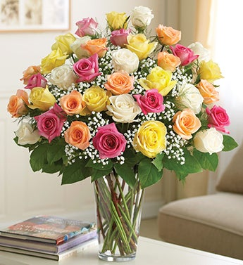 /four dozen roses in glass vase