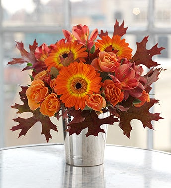 Brilliant orange Gerbera daisies in julep cup